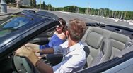 Young pair ride backward in cabriolet on street at sunny day Stock Footage