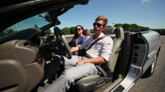 Couple in sunglasses sit in cabriolet with driver door open Stock Footage