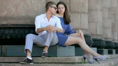 Young couple sit on steps near colonnade, fluff flies around Stock Footage