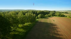 Balloons fly over wood and field against blue sky and sun Stock Footage