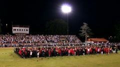 Cool shot of high school graduation with graduates tossing hats into the air Stock Footage