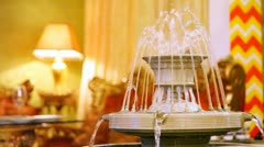 Fountain works in restaurant hall near carved sofa and table Stock Footage