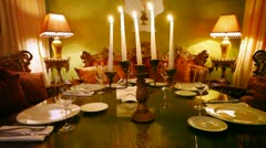Tableware stands on table on which light candles in restaurant Stock Footage