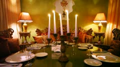 Five candles burn in table center in restaurant lounge Stock Footage