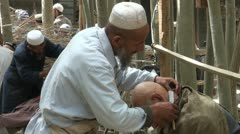 Traditional haircut using a knife in an Uyhgur village in Xinjiang, China Stock Footage