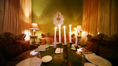 East sofas stands near table on which light candles Stock Footage