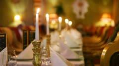 Burning candles in row stand on tables with white cloths Stock Footage
