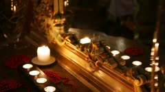 Burning candles and beads face a mirror in carved frame Stock Footage
