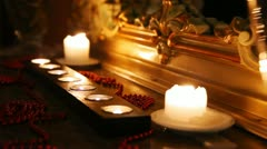 Burning candles and beads face mirror in carved frame in dark Stock Footage