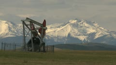 Oil industry, pump-jack and snow covered mountains Stock Footage