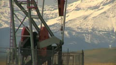 Oil industry, pump-jack and snow covered mountains long lens Stock Footage