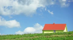 Cumulus clouds passing over yellow small house on the hill Stock Footage