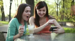 Two female friends with mobile phone in outdoors restaurant HD Stock Footage
