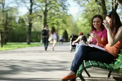 Two young college friends using a smart phone, outdoors, tracking shot NTSC - stock footage