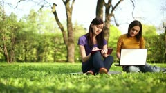 Two students working together with book and laptop outside, tracking shot HD Stock Footage