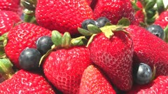 Strawberries and blueberries turning in pile Stock Footage