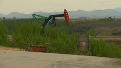 Oil industry, pump jack and highway traffic on hilly curve Stock Footage