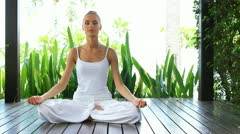 Woman in lotus position meditating Stock Footage
