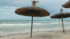 Storm the Mediterranean Sea and palm-leaf parasols on the beach in strong winds Stock Footage