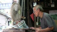 A man reads a Chinese newspaper on the streets Stock Footage