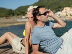 Couple relaxing on wooden pier by the sea, dolly shot NTSC Stock Footage