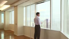 Businessmen looking out office window at city Stock Footage