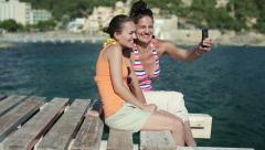 Female friends taking photo with cellphone on pier, dolly shot HD Stock Footage