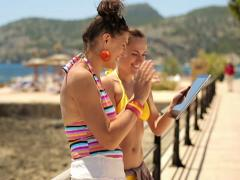 Female friends chatting on tablet computer, boardwalk by the sea NTSC Stock Footage