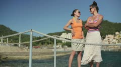 Two happy female friends chatting on pier by the sea, dolly shot HD Stock Footage