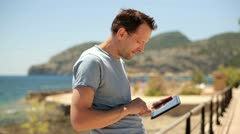 Happy young man with tablet computer, boardwalk by the sea HD Stock Footage
