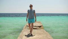 Man walking on stone pier by the beautiful sea HD Stock Footage
