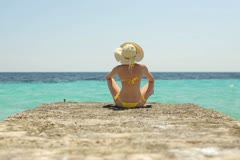 Sexy woman in bikini and summer hat sitting on stone pier NTSC Stock Footage