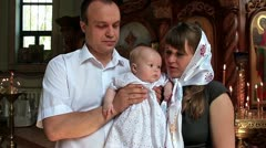 Mother and father with baby in orthodox church after christening ceremony Stock Footage