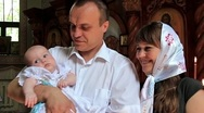 Mother and father with baby in orthodox church Stock Footage