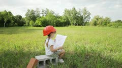 3s girl on the field with a picture house. Looking at camera - stock footage