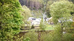 Chair lift crossing trees and water Stock Footage