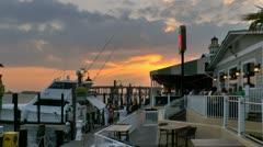 Sunset over Destin harbor marina next to dock side restaurant Stock Footage