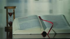 Holy Bible with hourglass 4 Stock Footage