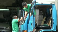 Two workers repair the windscreen of a truck in Hong Kong Stock Footage