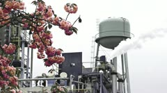 Water Tower Factory Mill Steam and Flowers 1 desat Stock Footage