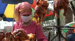 Female street vendor wears a headscarf on the streets of Hotan in China Stock Footage