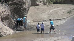 Chile Atacama Toconao wading in stream near rock Stock Footage