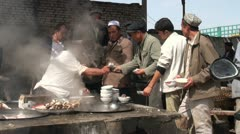 Pouring hot soups into bowls of hard workers at the livestock market in Kashgar - stock footage