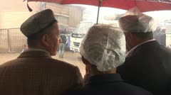 Three men are waiting for the rain to clear at the Kashgar livestock market Stock Footage