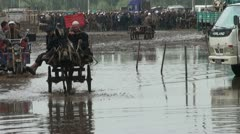 A donkey cart and tricycle ride through a massive pool after rain in Kashgar Stock Footage