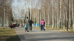 Young mother walking in a city park Stock Footage
