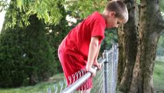 Cute young boy climbing over a fence to get into a backyard Stock Footage