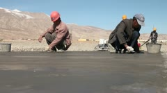 Migrant workers are busy flattening a road in remote Xinjiang, China Stock Footage