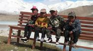 Cute Kyrgyz kids sit on a bench looking at the camera, at Karakul lake Stock Footage