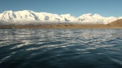 Waves at a beautiful Karakul lake with mountain ranges in background Stock Footage